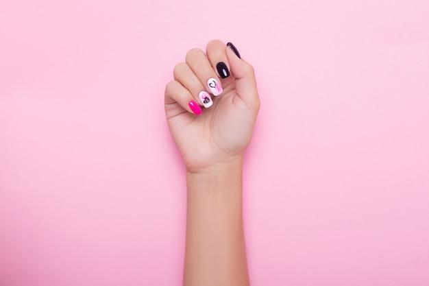 創造的なマニキュアの爪を持つ女性の手