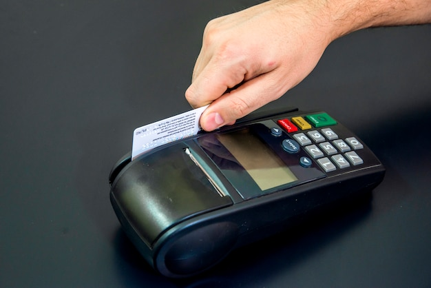 Female hand with credit card and bank terminal, card machine or pos terminal with inserted blank white credit card isolated on black background