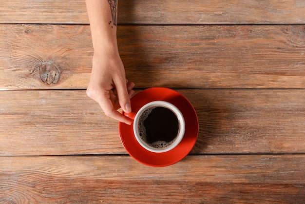 Женская рука с чашкой ароматного кофе на деревянном столе, вид сверху