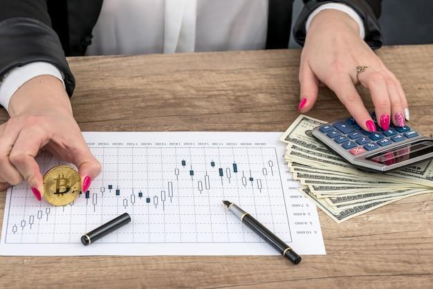 ドル、ビットコイン、ビジネスグラフと女性の手