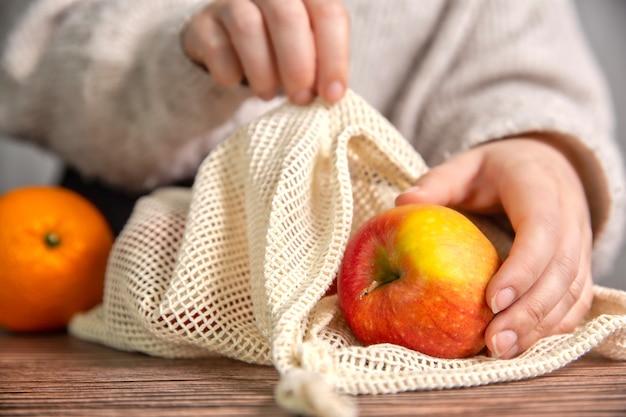 신선한 과일로 식료품 쇼핑을위한 환경 친화적 인 그물 가방이있는 여성 손