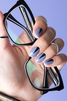 Female hand with fashionable manicure holding black glasses