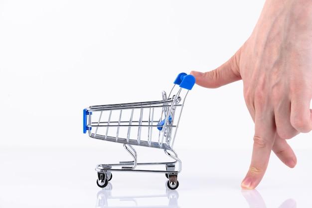 Женская рука с пальцами в виде идущего человека, толкая тележку для покупок, изолированные на белом фоне. скопируйте пространство.