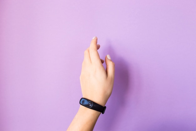 Female hand with a fitness bracelet. on a bright purple background. healthy lifestyle and fitness concept