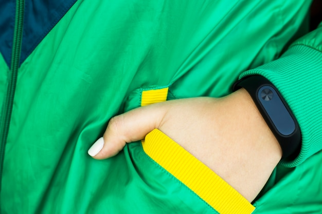 Female hand with a fitness bracelet. in a sports bright green jacket for sports. healthy lifestyle and fitness concept