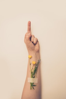 Female hand with flowers on her wrist showing middle finger gesture