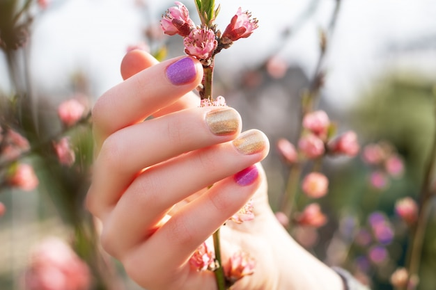 Female hand with gold and purple nail design holding blossom branch.