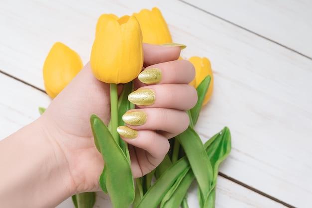 金色のネイルデザインの女性の手。キラキラゴールドのマニキュアマニキュア。女性の手は白い木製の背景に黄色の春のチューリップを保持します。コピースペース