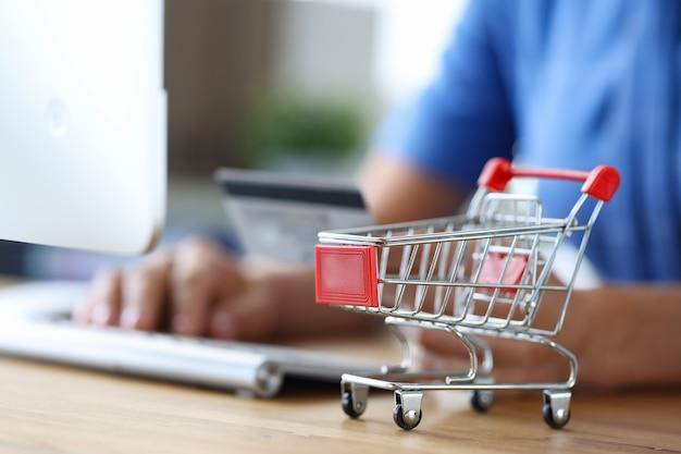 키보드와 쇼핑 트롤리 온라인 쇼핑 컨셉이 있는 여성 손