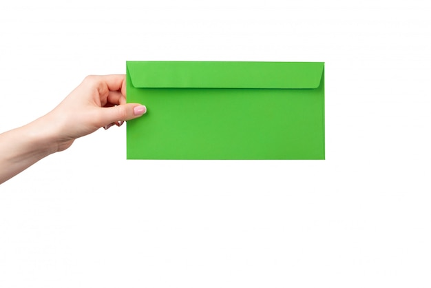 Female hand with manicure holding green envelope