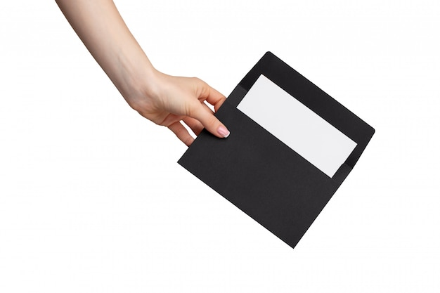 Female hand with manicure holding open black envelope