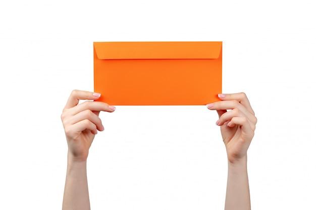 Female hand with manicure holding orange envelope