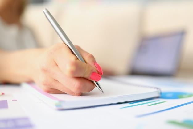 매니큐어가 있는 여성 손은 은색 펜으로 메모를 작성합니다. 여성은 문자 거리를 씁니다.