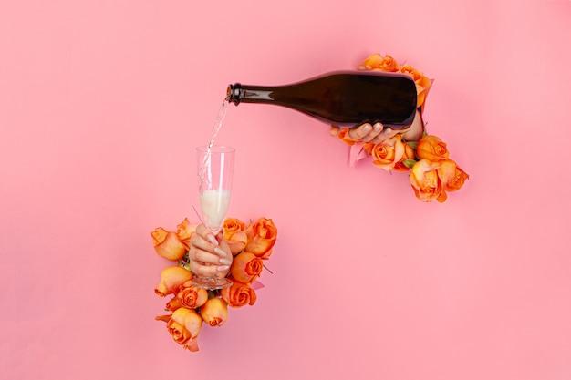 バラで飾られた破れた紙の穴からグラスにシャンパンを注ぐマニキュアで女性の手