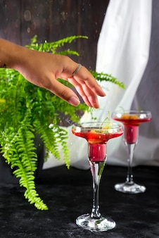 Female hand with margarita cocktail garnished with a macaroons and berries on a dark backg
