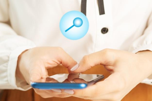 Женская рука с мобильным телефоном и значками увеличительного стекла, концепция поиска в интернете через смартфон