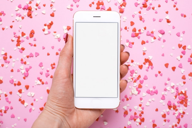 Female hand with mobile phone on with pink and red hearts