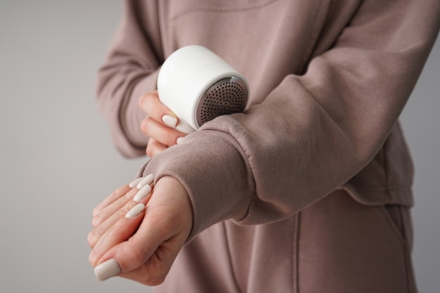 Female hand with modern fabric shaver and clothes on color background. close-up.