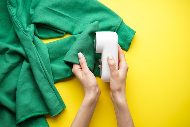 Female hand with modern fabric shaver and sweater on color background. top view.
