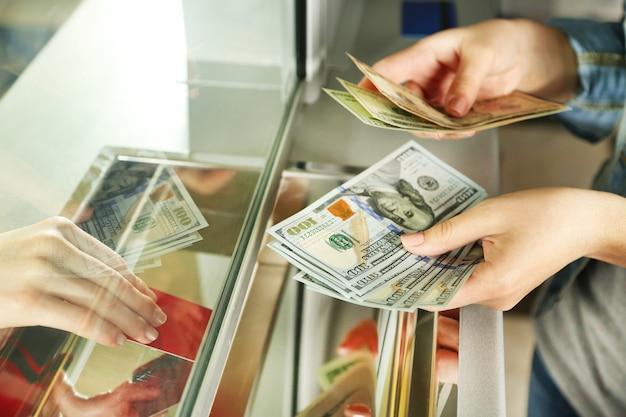 현금 부서 창에서 돈으로 여성 손입니다. 환전 개념