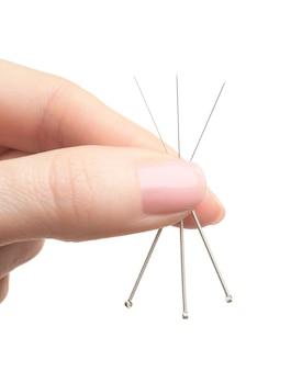 白い表面に鍼治療のための針を持つ女性の手、クローズアップ