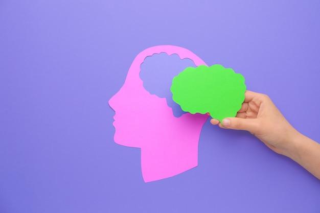 色の背景に紙の脳と人間の頭を持つ女性の手。神経学の概念