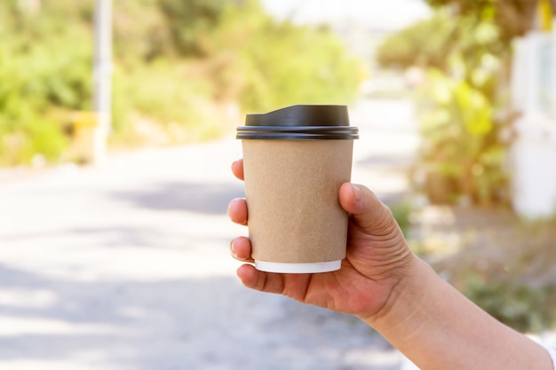 Female hand with paper cup of coffee take away,paper coffee cups in women's hands with perfect manicure
