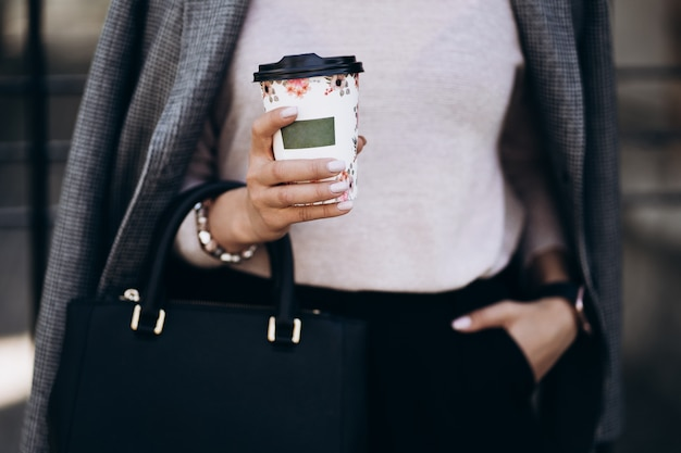 コーヒーの紙コップを持つ女性の手は路上で奪います。暗いズボンとクリーミーなセーターのビジネスウーマン。ファッションのコンセプトです。女性のビジネススタイル。高解像度。