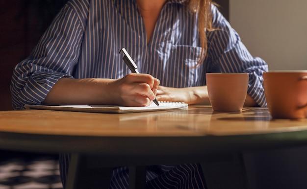 Женская рука с ручкой, делая заметки, написание планов в дневнике на деревянном столе с кофейными чашками