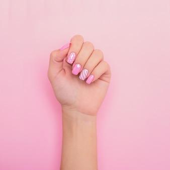Женская рука с розовыми ногтями маникюра, дизайн сердца