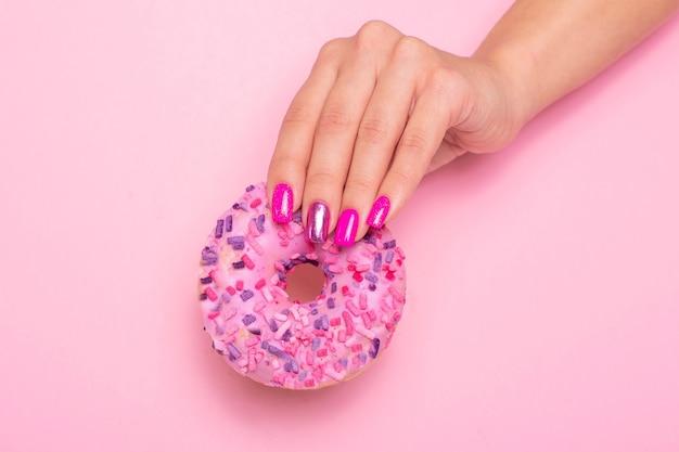甘いイチゴのドーナツを保持しているピンクのマニキュアの爪を持つ女性の手