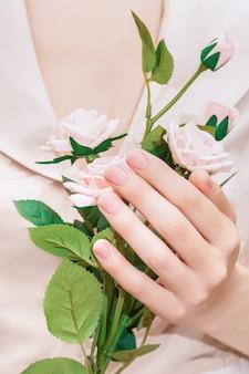 女性手与粉红色指甲设计。女手捧玫瑰花束。女人手上粉红色的织物背景。