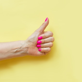 Female hand with pink nail on yellow..