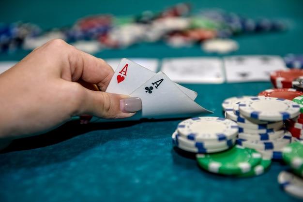 トランプとポーカーチップを持つ女性の手がクローズアップ