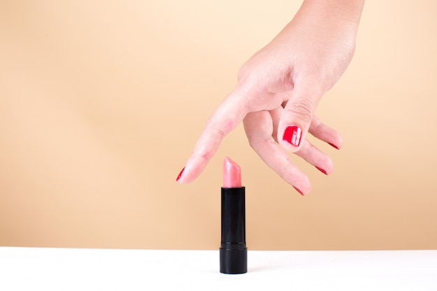 Female hand with red fingernails taking lipstick