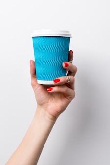 コーヒーの紙コップを保持している赤いマニキュアで女性の手。