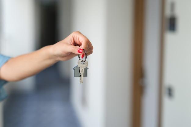 家の鍵のクローズアップを保持している赤いマニキュアと女性の手