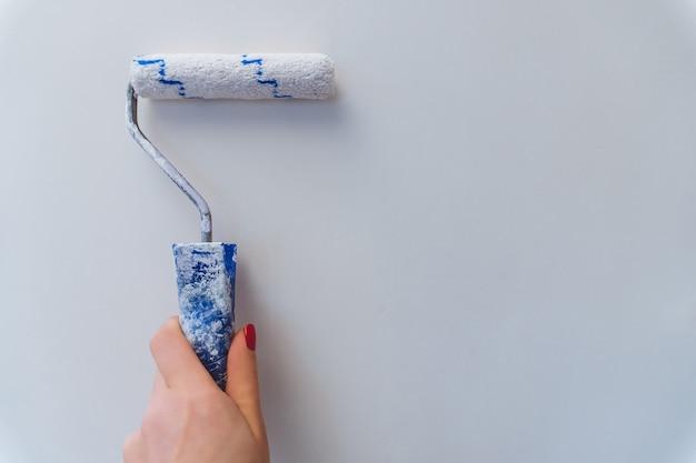 Женская рука с красным маникюром держит ролик и окрашивает стены в белый цвет, ремонт и улучшение дома.