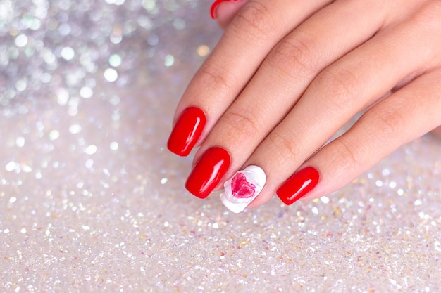 Женская рука с красными ногтями маникюра, дизайн сердца
