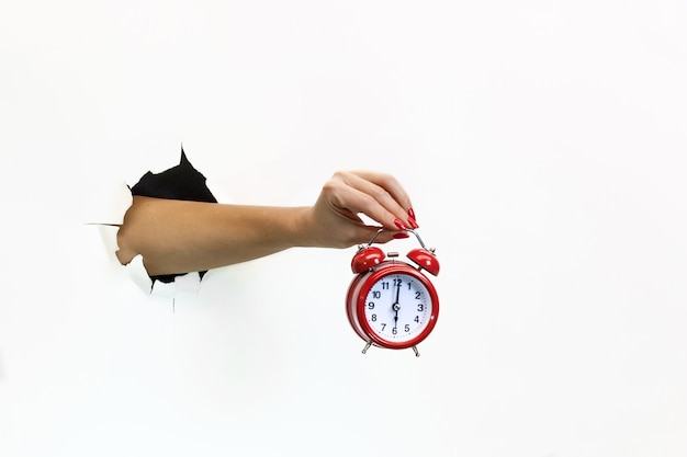 A female hand with red manicure through torn white paper holds a red alarm clock. hand through torn white paper. hand holding a red alarm clock