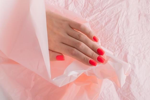 赤いネイルデザインの女性の手。しわくちゃの紙の背景に女性の手。