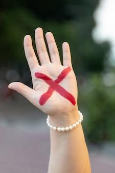 ブラジルのリオデジャネイロでの家庭内暴力に対するキャンペーンを象徴する赤いxの女性の手。