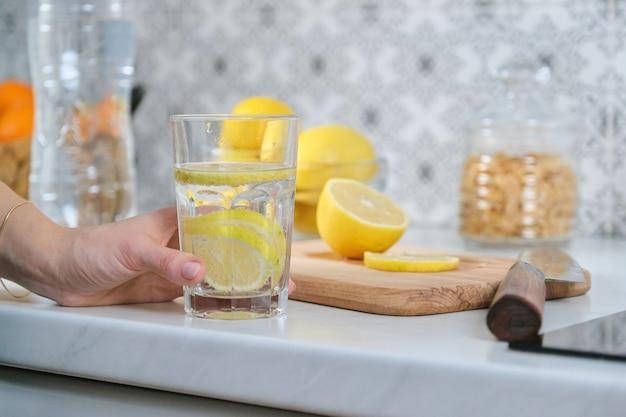 Женская рука с ломтиком лимона на кухне, со свежеприготовленным газированным напитком с лимоном