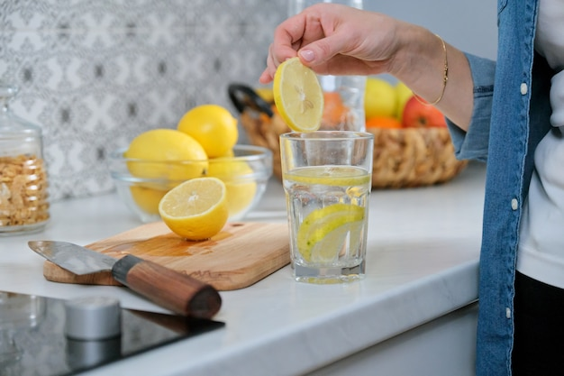 갓 만든 음료와 함께 부엌에서 레몬 조각으로 여성 손