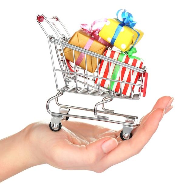 白で隔離の贈り物でいっぱいの小さなショッピングカートを持つ女性の手