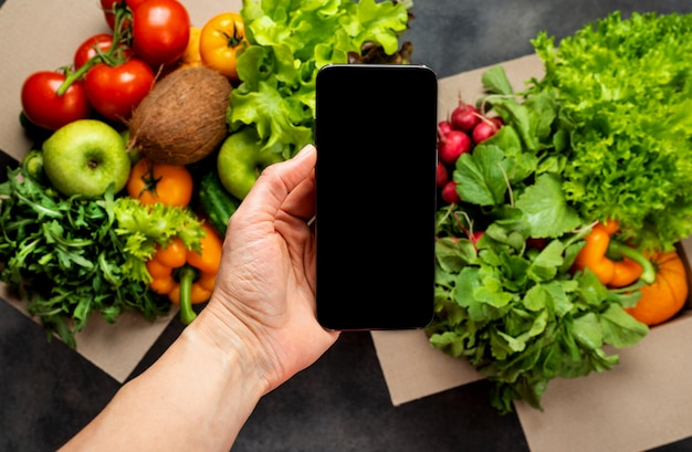 Female hand with smartphone and full boxes of different fresh organic vegetables