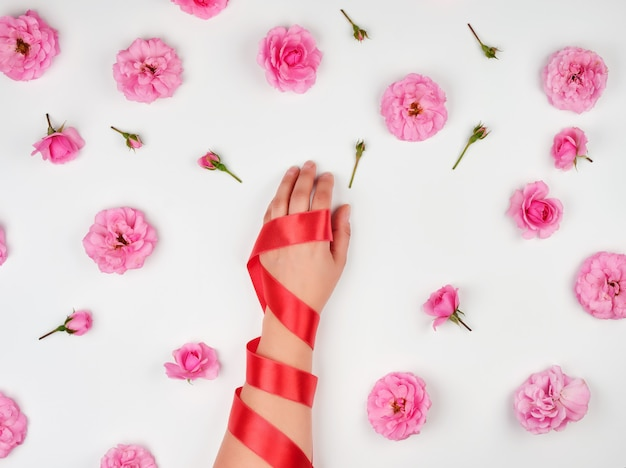 Female hand with smooth skin wrapped with red silk ribbon