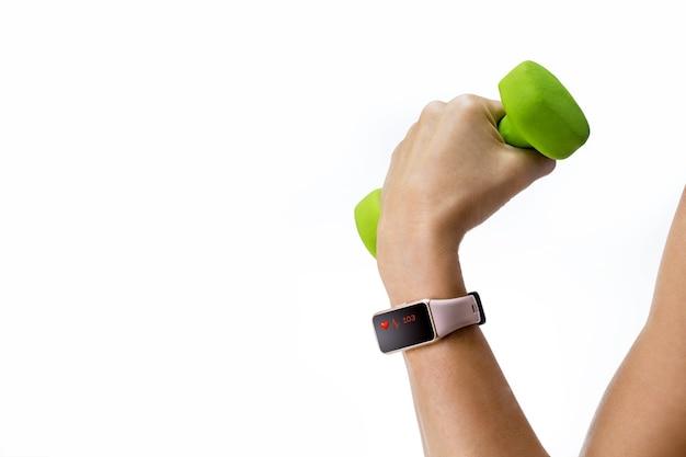 체육관에서 아령을 드는 스포츠 스마트 시계와 여성 손.