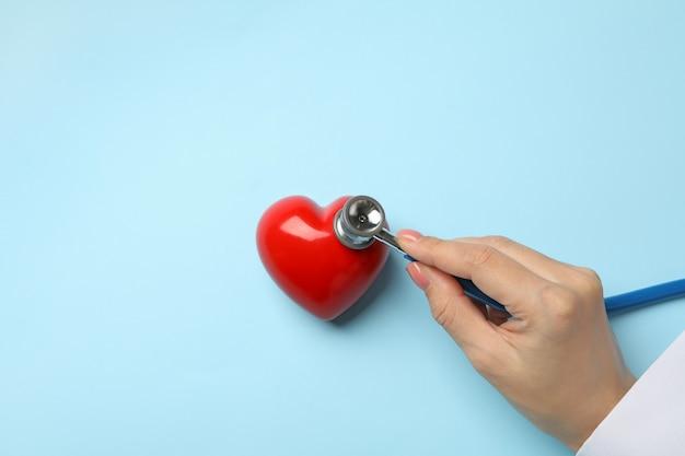 聴診器で心拍をチェックする女性の手