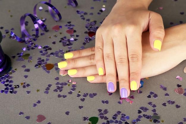 밝은 배경에 세련된 화려한 손톱이 있는 여성 손
